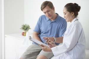 Medicaid Eligibility Doctor Helping Patient Fill Out Paperwork Image